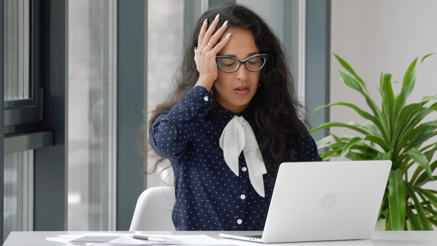 Shocked frustrated mixed race business woman student feel stressed look at computer screen.