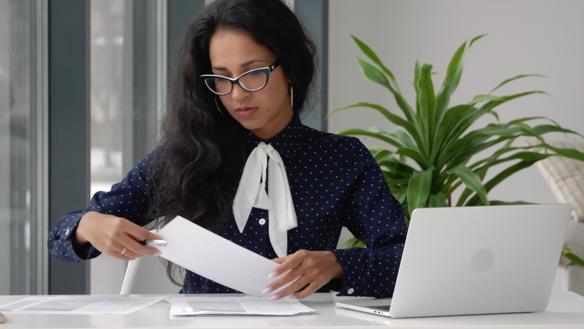 Female entrepreneur reading documents, analyzing financial papers, preparing audit report at workplace. Serious young mixed race businesswoman checking corporate paperwork correspondence Royalty-Free Stock Footage #1067293093