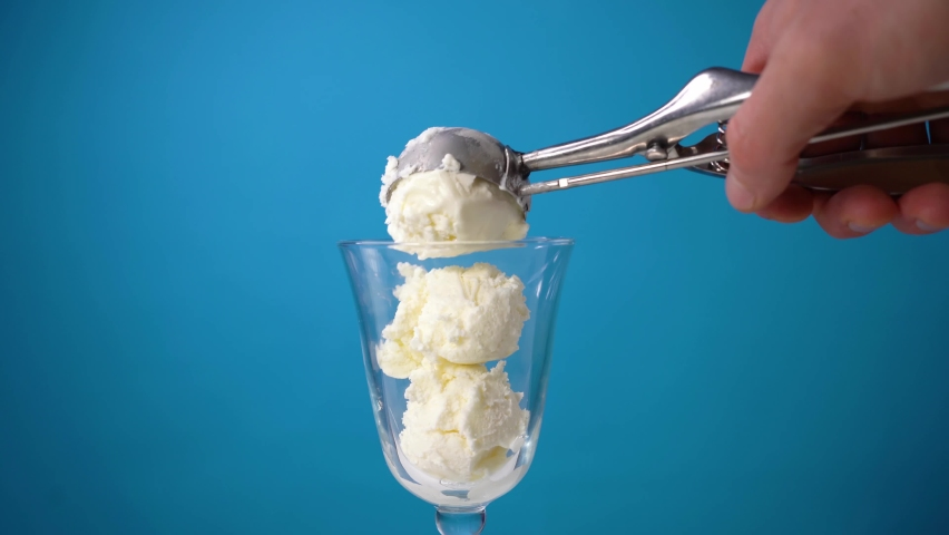 Place vanilla ice cream in a glass. Make balls of white ice cream with a special spoon. Cooking delicious ice cream on a blue background. Summer dessert in a cafe. | Shutterstock HD Video #1067297134