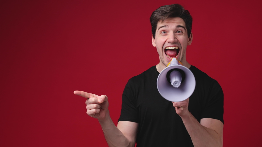 Cheerful shocked young man 20s years old in casual black t-shirt posing isolated on red background studio. People sincere emotions lifestyle concept. Pointing index finger aside screaming in megaphone