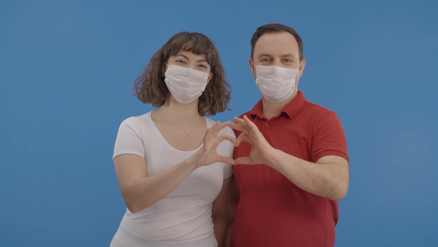 Happy couple in medical masks made heart shape with their hands. Concept of Valentine's Day celebration, romantic relationships, newlyweds, sincere feelings and love.Blue background. Royalty-Free Stock Footage #1067306395