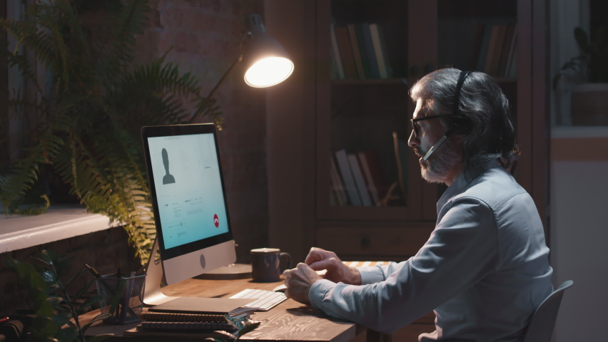 Side-view waist-up footage of adult call center operator speaking via headset sitting at desk in front of computer monitor screen in dark empty office at night | Shutterstock HD Video #1067327818