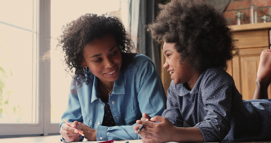 Affectionate loving young african american mother lying on heated floor with small adorable child daughter, communicating chatting discussing life event while drawing pictures in paper album indoors.