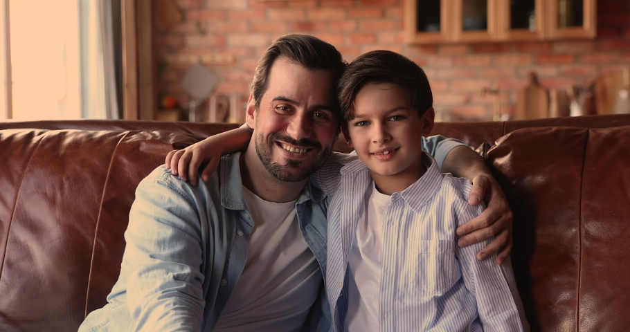 Happy young affectionate dad cuddling school aged adorable little boy son, looking at camera. Smiling sincere loving two different male generations family showing sweet tender caring feelings at home. Royalty-Free Stock Footage #1067336341