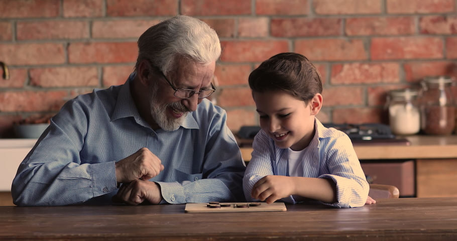 Happy elderly mature 60 hoary man in eyeglasses playing checkers draughts on wooden board with joyful little grandson, enjoying creative game on weekend leisure time, having fun together at home. | Shutterstock HD Video #1067337310