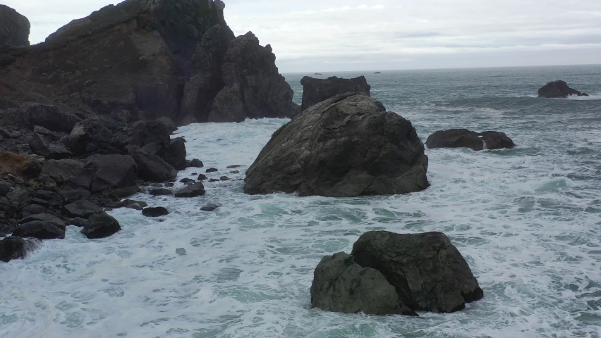 The cold, nutrient-filled waters of the Pacific Ocean crash against the rocky Northern California coast in Humboldt. The scenic Pacific Coast Highway runs along this amazing part of the west coast. Royalty-Free Stock Footage #1067337388