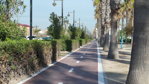 Spain, Valencia - December 29, 2020: Cyclists riding along bicycle road path in tourist place of Valencia through seafront promenade. Sport lifestyle, tourism concept. Cycling infrastructure. Spain