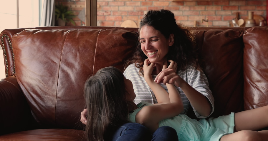 Mother play with cute daughter. Happy kid young mom tickling each other while rest on sofa at home. Spend free leisure time together enjoy playtime. Younger generation, offspring, family bond concept Royalty-Free Stock Footage #1067349586