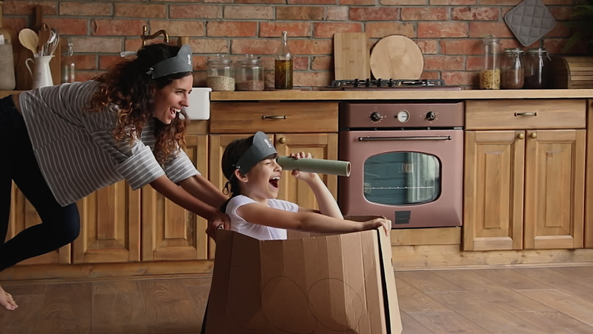 Young mother ride little cute daughter sit in carton box, kid girl looking in paper tube binocular enjoy creative game with mom in kitchen. Creativity, handmade plaything, having fun at home concept Royalty-Free Stock Footage #1067355169
