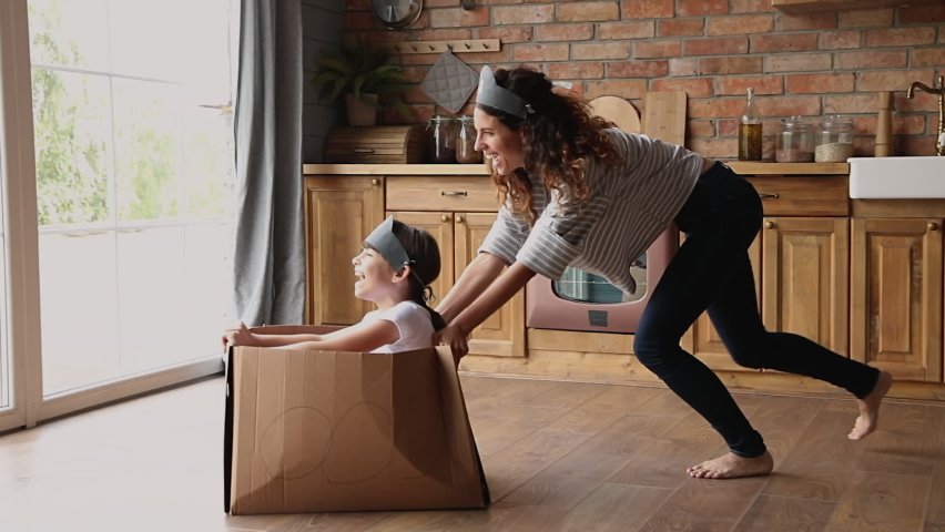 Active family play games at modern warm kitchen, young mom riding small daughter while she sitting inside of cardboard box, celebrate relocation day to new home, spend quarantine time creative concept Royalty-Free Stock Footage #1067355175