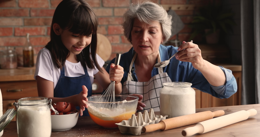 60s elderly female babysitter teach little girl to cook. Loving grandmother and small granddaughter prepare family recipe cake for event, stirring eggs make dough enjoy process. Hobby, cookery concept