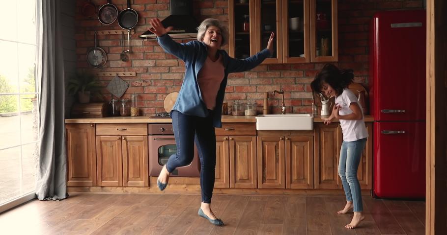 Active 60s grandma joyful 10s grandkid having fun in kitchen dancing listen rock music pretend be superstar, kid shake head imagine play guitar enjoy carefree weekend with granny. Home hobby concept