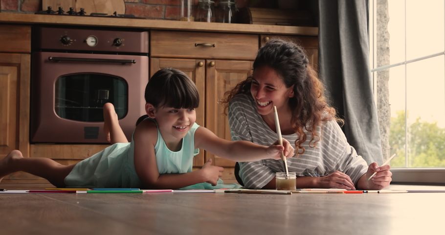 Young mom little daughter enjoy leisure activity lying on warm wooden floor in cozy kitchen holding paintbrushes create drawings painted with watercolor paint. Children development, home hobby concept Royalty-Free Stock Footage #1067355352