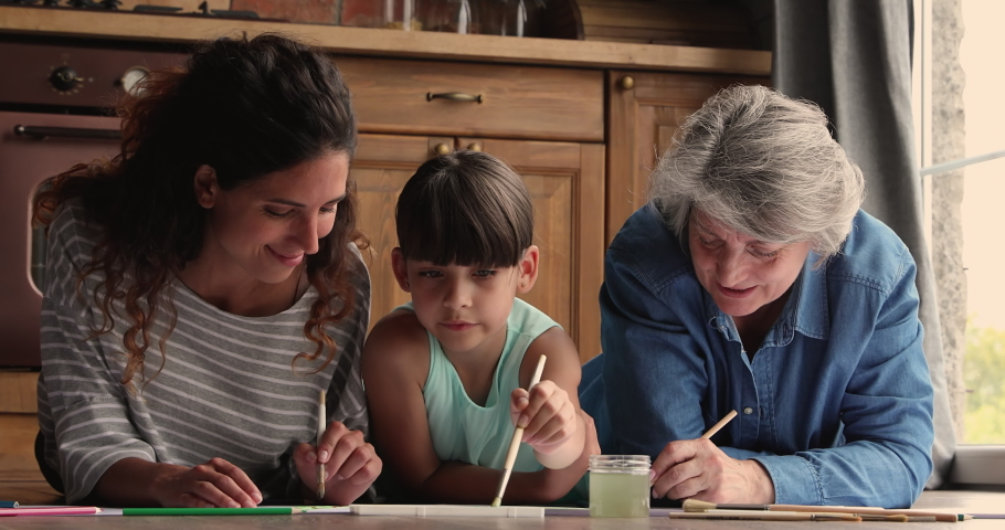 Three gen family diverse women granny mom and child spend weekend together gathered in kitchen lying on warm floor hold paint brushes drawing on paper enjoy leisure. Kid development home hobby concept Royalty-Free Stock Footage #1067355373
