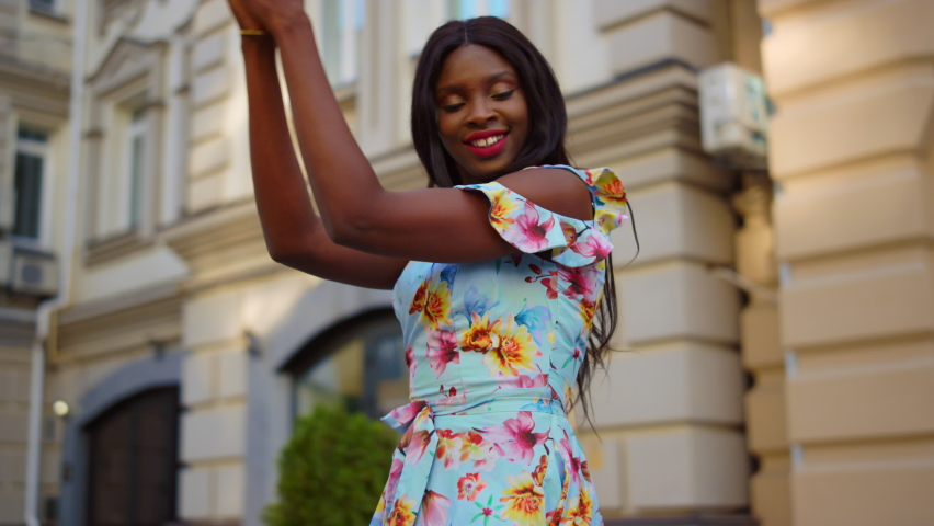 African american girl making body moves in city. Positive african female professional practicing latino dance outdoors. Energetic afro woman dancing bachata on street in slow motion.