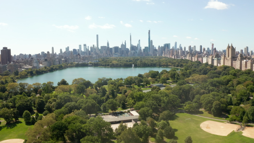 Manhattan Skyscrapers revealing behind beautiful Green Nature with Trees and Lake in Central Park, New York City, Aerial Wide View