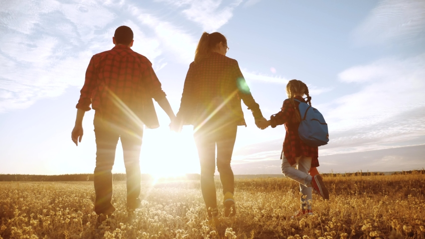 Happy family walking in the park. friendly family kid dream concept. mom dad and child kid walk in the park on green lifestyle grass outdoors. happy family with their backs walking in the park | Shutterstock HD Video #1067374385