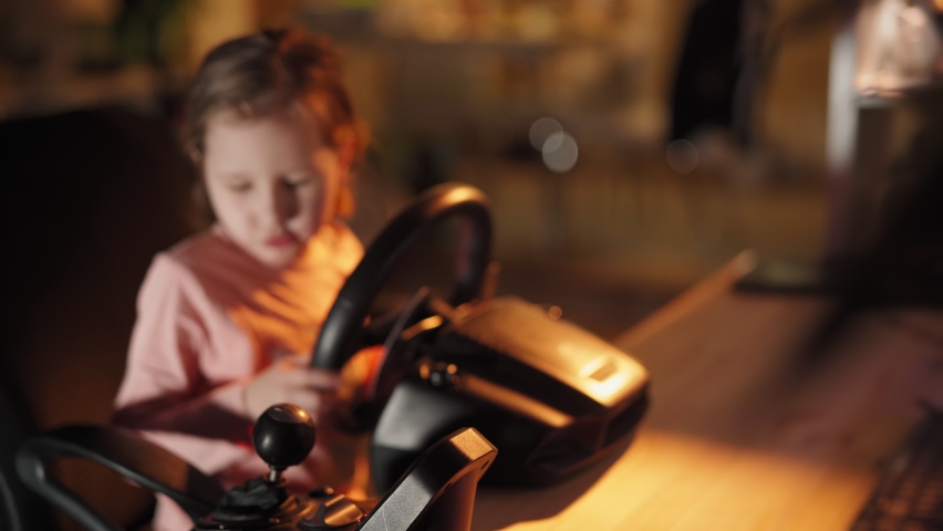 A little girl plays computer games, a child plays a racing game on a car simulator. concept of video games The newest gadgets | Shutterstock HD Video #1067398667