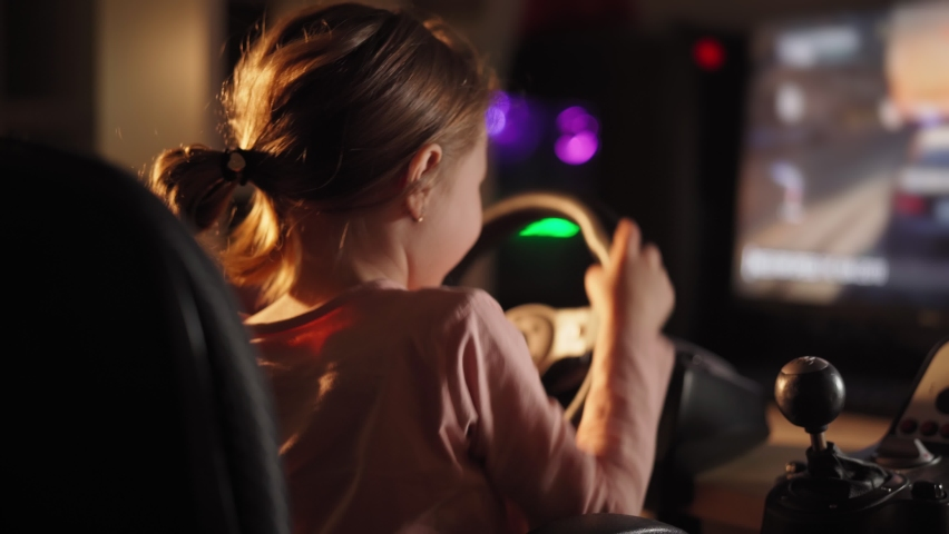 A little girl plays computer games, a child plays a racing game on a car simulator. concept of video games The newest gadgets | Shutterstock HD Video #1067398679