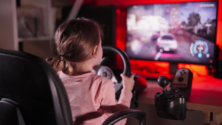 A little girl plays computer games, a child plays a racing game on a car simulator. concept of video games The newest gadgets | Shutterstock HD Video #1067398715