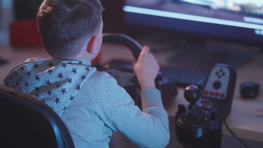 A small boy plays computer games, a child plays a racing game on a car simulator. concept of video games The newest gadgets  | Shutterstock HD Video #1067398718