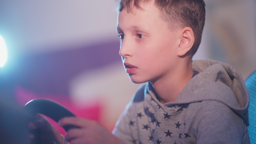 A small boy plays computer games, a child plays a racing game on a car simulator. concept of video games The newest gadgets  | Shutterstock HD Video #1067398724