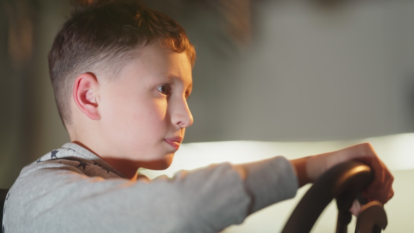 A small boy plays computer games, a child plays a racing game on a car simulator. concept of video games The newest gadgets  | Shutterstock HD Video #1067398745