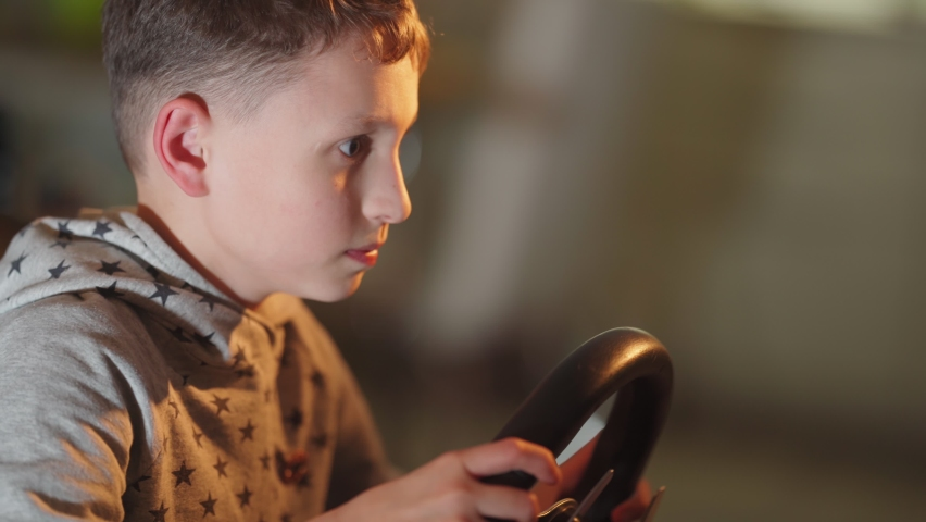 A small boy plays computer games, a child plays a racing game on a car simulator. concept of video games The newest gadgets  | Shutterstock HD Video #1067398766