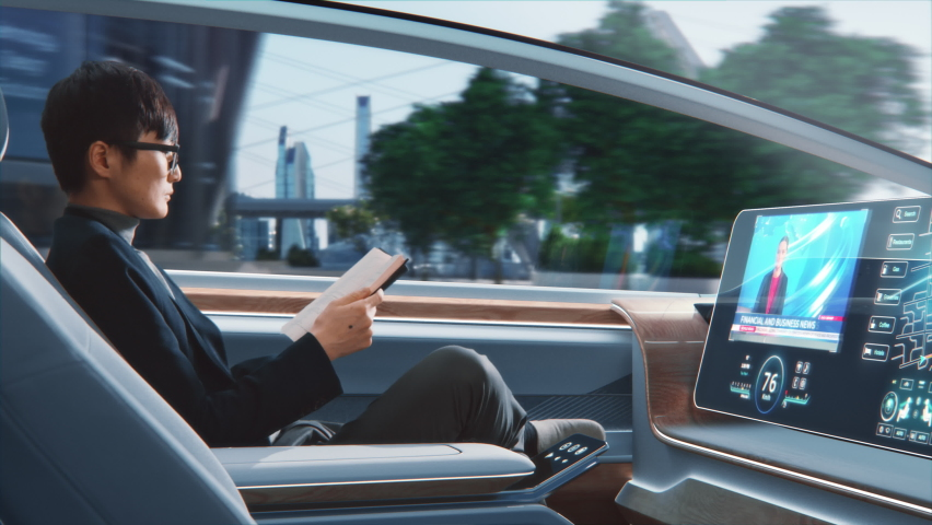 Futuristic Concept: Handsome Stylish Japanese Businessman in Glasses Reading Notebook and Watching News on Augmented Reality Screen while Sitting in a Autonomous Self-Driving Zero-Emissions Car.