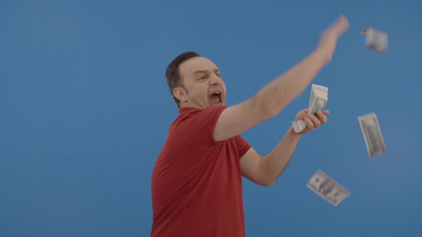 Young man with beard in front of a blue background who is cheerfully gesturing while handing out money. Concept of to pour money without thinking. It makes it rain by throwing money into the air.   Royalty-Free Stock Footage #1067441891