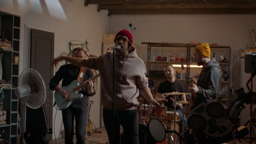 WIDE Friends playing music during their rock band rehearsal repetition inside a garage. Vocals, guitars and drums. Shot with 2x anamorphic lens | Shutterstock HD Video #1067449685