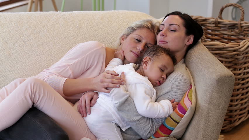 Same sex couple sleeping on their sofa with their baby son sleeping on one of their chests.