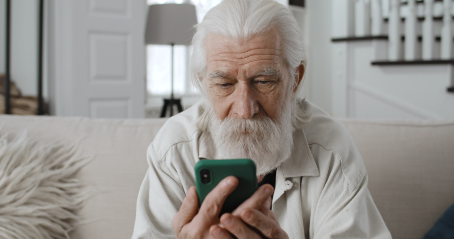 Close up view of old grey haired man chatting with family while looking at phone sreen.Cheerful bearded male retiree reading message and smiling whilesitting on sofa at home. | Shutterstock HD Video #1067486273
