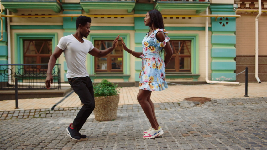 Closeup focused afro man and woman dancing bachata on street. African american couple making moves outdoors. Full length cute african professional dancers performing latino dance in city.