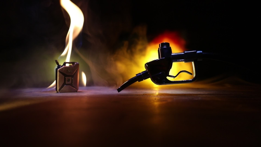Creative concept. Silhouette of gasoline pistol miniature on dark toned foggy background. Close up. Industrial decorated elements on background. Selective focus | Shutterstock HD Video #1067525558