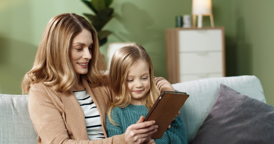 Happy mom with little daughter sitting hugging on sofa at home and watching cartoons online using tablet. Royalty-Free Stock Footage #1067530379