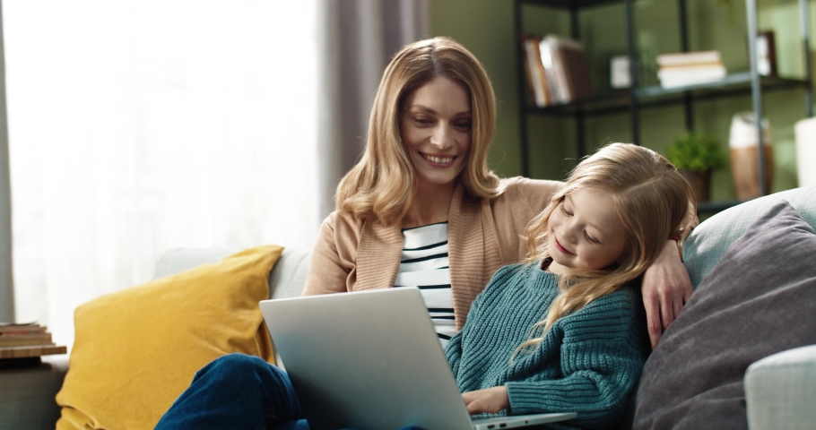 Happy mom with little daughter sitting hugging on sofa at home and watching cartoons online using laptop. Royalty-Free Stock Footage #1067530385