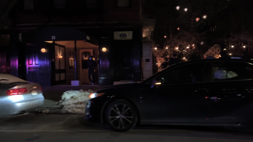 NYC, USA - FEB 12, 2021: NYPD traffic police towing cars illegally parked outside nightlife bars and clubs winter snow East Village Manhattan New York City.