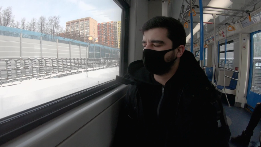 Moscow, Russia, 02.16.2021: a young European brunette in a mask rides a Moscow metro train. the guy looks out the window. winter cold day | Shutterstock HD Video #1067551724