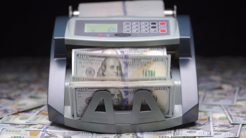 Currency counting machine counts 100 dollar bills or USD banknotes. Cash bill counter money machine stands on scattered dollars. Automatic mechanism for bank financial operations. Finance concept. Royalty-Free Stock Footage #1067563001