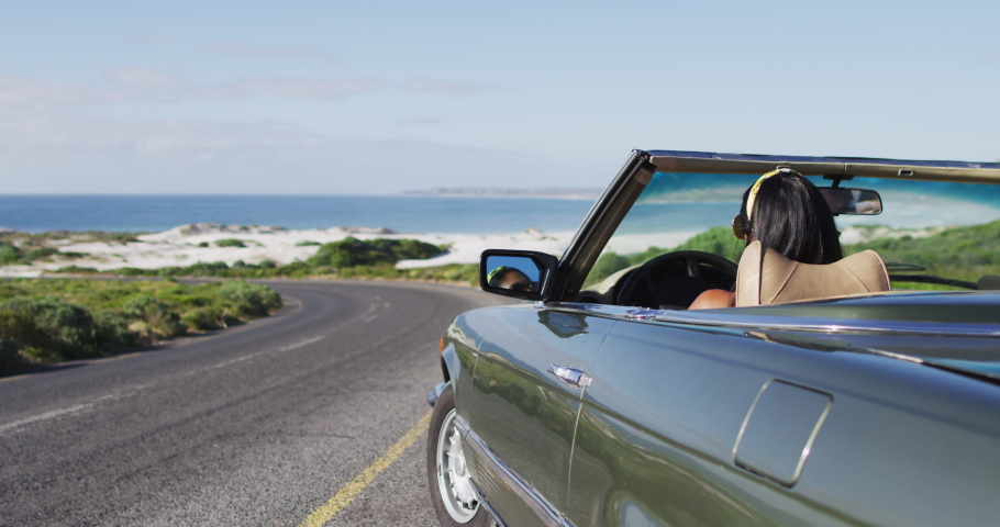 African american woman wearing sunglasses sitting in the convertible car on road. road trip travel and adventure concept | Shutterstock HD Video #1067566643