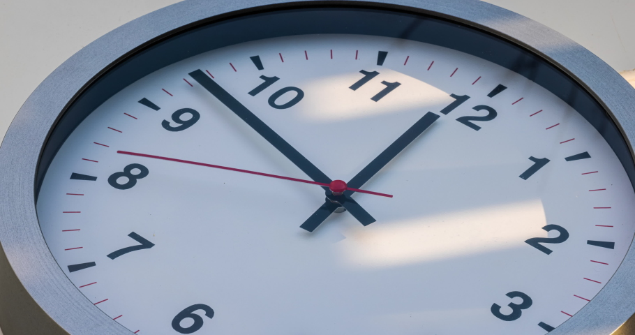 Wall clock show the running time. Time lapse on a modern wall clock at noon.  Close up to a wall clock, with running time pointer. Sun and sky reflecting in the watch during the time passing by | Shutterstock HD Video #1067568551
