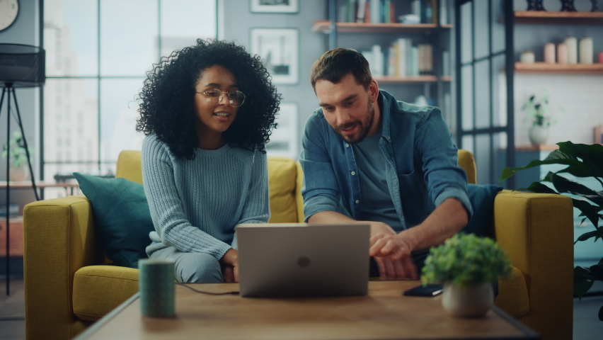 Diverse Multiethnic Couple are Sitting on a Couch Sofa in Stylish Living Room and Choosing Items to Buy Online with Laptop Computer. Friends or Colleagues are Discuss Work Projects and Give High Five. Royalty-Free Stock Footage #1067577215