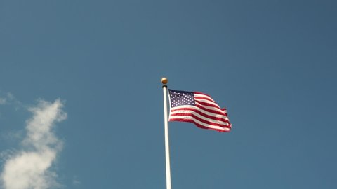 slow motion view of an American flag blowing in the wind on pole with shadows on the surface, blue sky with clouds. conceptual photo, top copy space