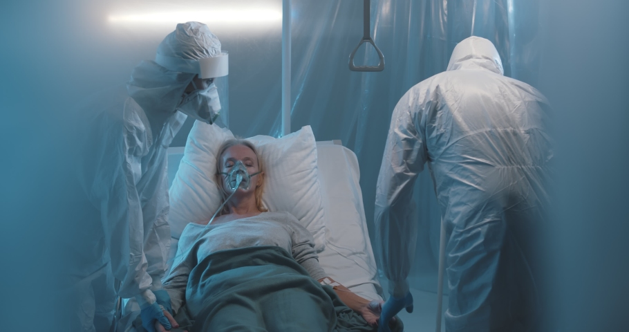 Doctors and nurses working hard to treat covid-19 infected patient in ICU. Medical staff in protective overall taking care of sick woman in oxygen mask lying on bed in isolation ward Royalty-Free Stock Footage #1067618669