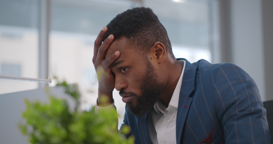 Close up of stressed and upset african man with laptop working at office. Portrait of afro-americna businessman receiving email with bad news feeling frustrated sitting at desktop in office   Shutterstock HD Video #1067618699