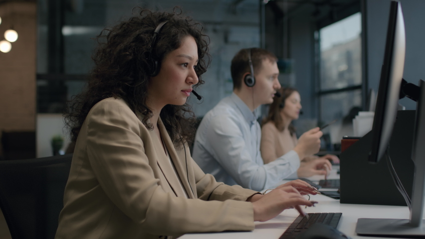 Call center and helpful customer service. Use desktop pc at computer table and phone line at modern co-working. Diverse group of workers talks on sale hotline. Busy seller at agency office close-up | Shutterstock HD Video #1067649053