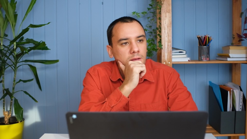 Thoughtful concerned man working on laptop computer looking away thinking solving problem at home office Royalty-Free Stock Footage #1067665469