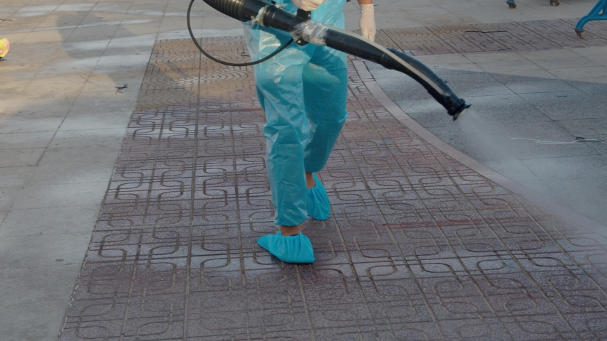 A man in a special protective suit disinfects the stage, tables and chairs, before the performance, man does the treatment and produces sprays of chemicals on the surface from the coronavirus. Royalty-Free Stock Footage #1067684264