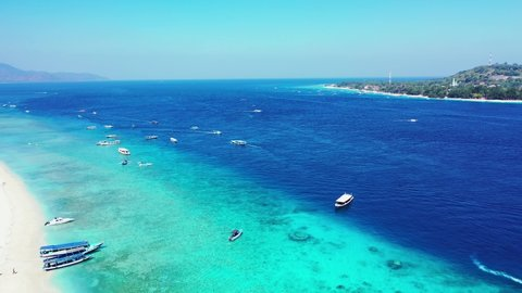 A calming sight of the wide blue sea during a sunny day with several boats sailing nearby a tropical island and a white sand beach, tracking forward in slow motion.
